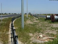 Non-frangible pole placed within deflection zone of wire rope barrier.