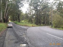 ...in fact it bends right. Side road should be partially sealed, with splitter island and edge line on main road.